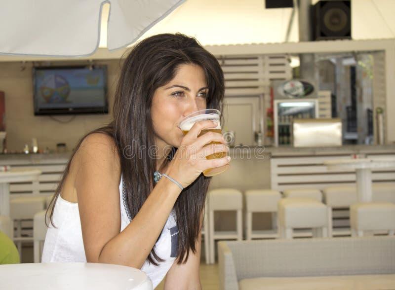 Portrait de la jeune belle femme buvant de la bière régénératrice froide au café images stock