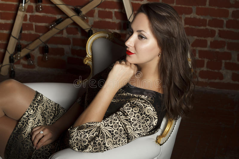 Portrait de la jeune belle femme de brune s'asseyant dans la chaise comme a photographie stock