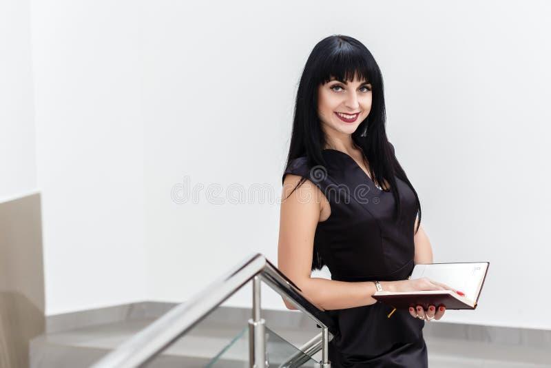 Portrait de la jeune belle femme heureuse de brune habillée dans un fonctionnement noir de costume avec un carnet, se tenant dans photos stock