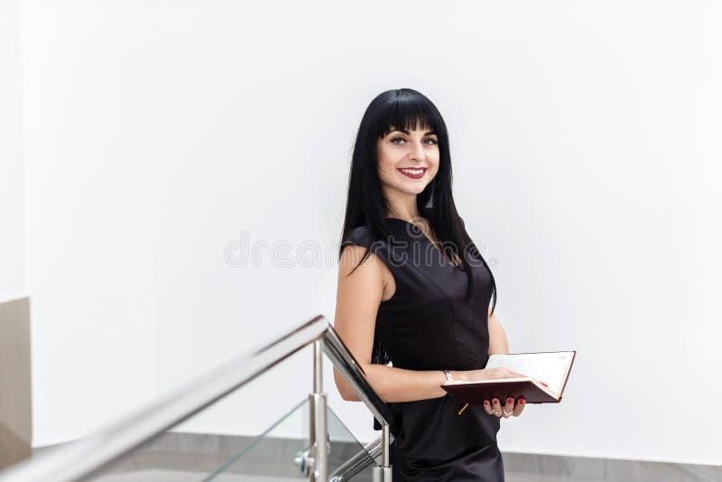 Portrait de la jeune belle femme heureuse de brune habillée dans un fonctionnement noir de costume avec un carnet, se tenant dans photo libre de droits