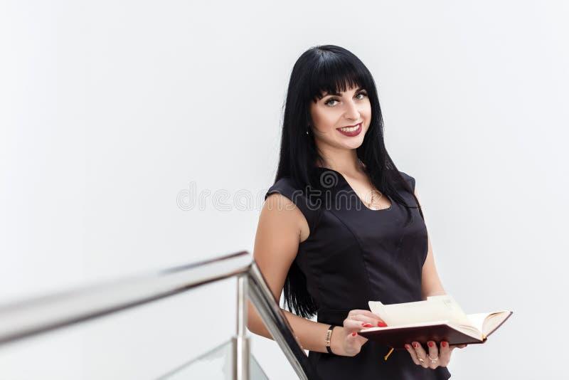 Portrait de la jeune belle femme heureuse de brune habillée dans un fonctionnement noir de costume avec le carnet, se tenant dans image stock