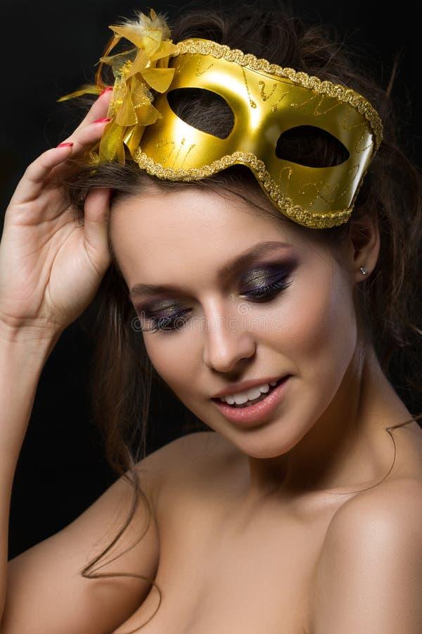 Portrait de la jeune belle femme portant le masque d'or de partie photos stock