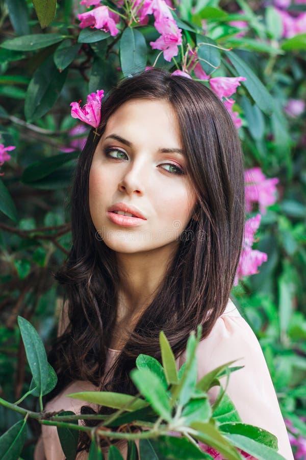 Portrait de la jeune belle femme posant parmi les arbres de floraison photo stock