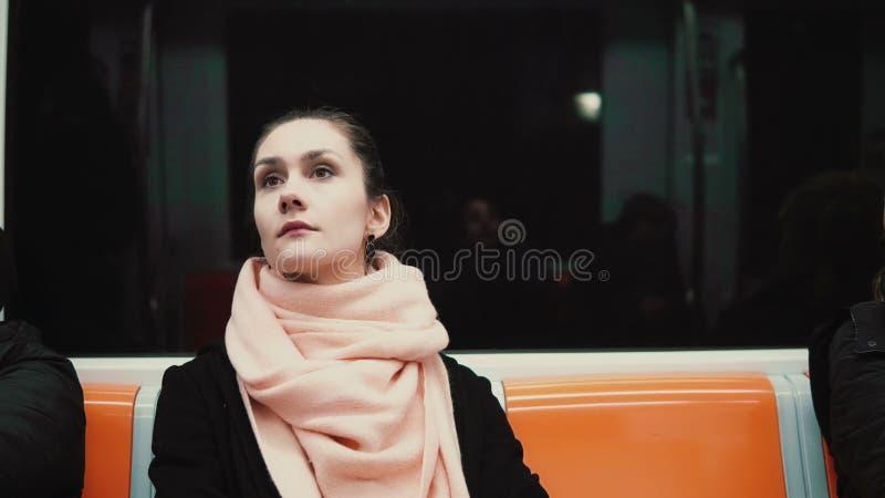 Portrait de la jeune belle femme s'asseyant dans le souterrain La fille attirante va travailler à côté de transport en commun image stock