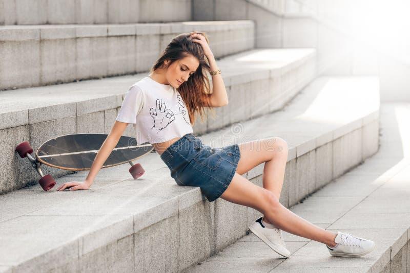 Portrait de la jeune belle fille à la mode posant sur les escaliers concrets photo stock