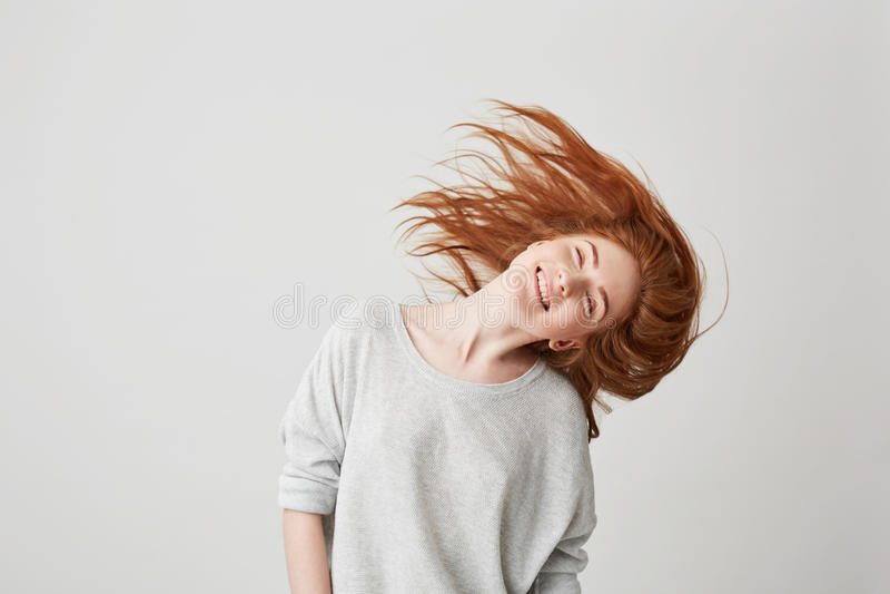 Portrait de la jeune belle fille rousse gaie souriant avec les yeux fermés secouant la tête et les cheveux au-dessus du fond blan photos stock