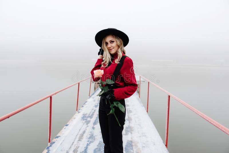 Portrait de la jeune belle position de femme sur le pilier et de tenir la rose rouge en hiver en brouillard photos libres de droits