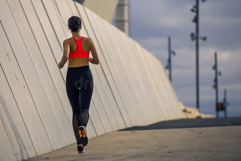 Portrait de la jeune et attirante femme courant le long du mur en parc urbain photos stock