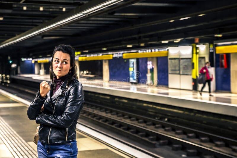 Portrait de la jeune et attirante femme se tenant dans la station de métro et attendant le train photo libre de droits