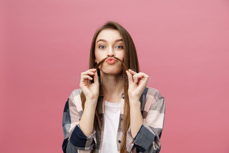 Portrait de la jeune femme adorable folle jouant avec ses poils fille émotive d'isolement sur le fond blanc photographie stock libre de droits