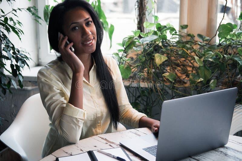 Portrait de la jeune femme africaine détendant en café avec l'ordinateur portable et faisant l'appel téléphonique, le mode de vie photo stock