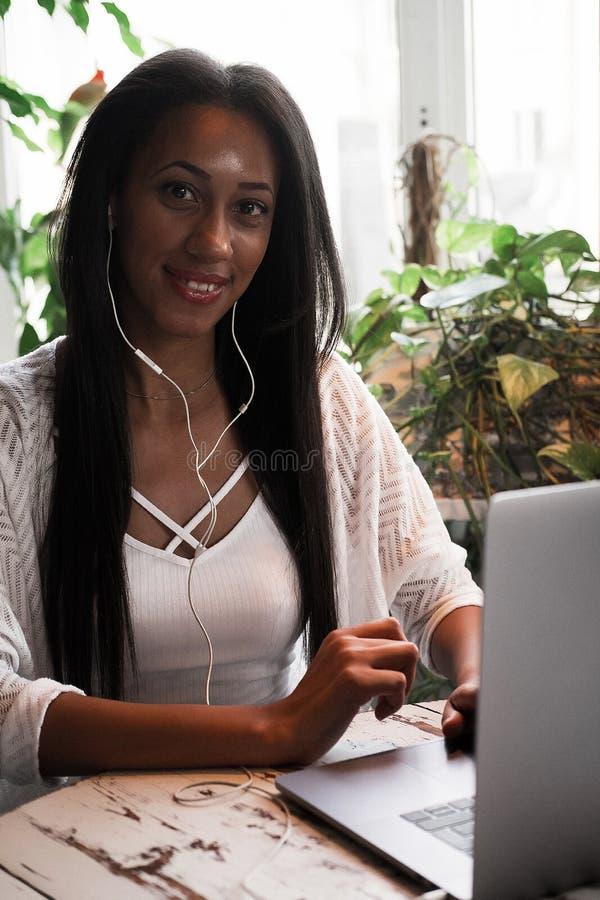 Portrait de la jeune femme africaine de sourire s'asseyant dans un café avec l'ordinateur portable, concept de mode de vie photo stock