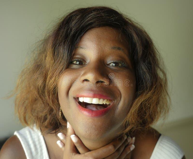 Portrait de la jeune femme afro-américaine noire heureuse et belle posant le regard gai de sourire avec du charme et espiègle à l photos stock