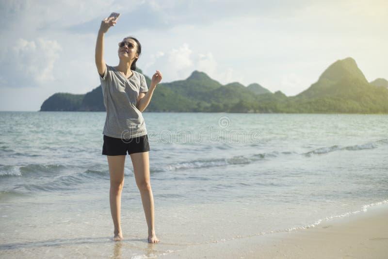 Portrait de la jeune femme asiatique à l'aide du téléphone intelligent à la plage Concept de technologie fond brouillé de mer de  photos stock