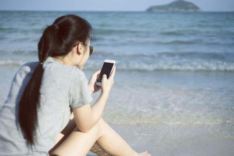 Portrait de la jeune femme asiatique à l'aide du téléphone intelligent à la plage Concept de technologie fond brouillé de mer de  photo stock