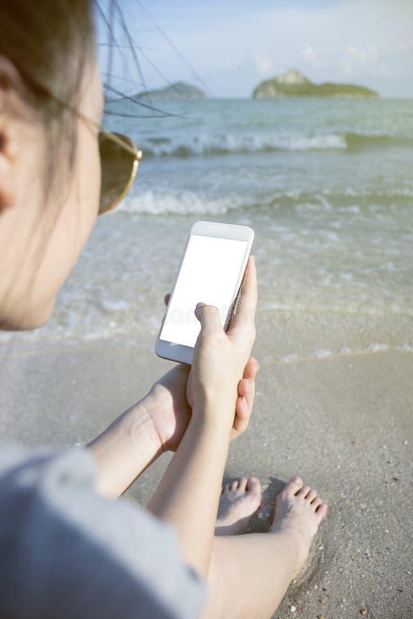 Portrait de la jeune femme asiatique à l'aide du téléphone intelligent à la plage Concept de technologie fond brouillé de mer de  image libre de droits