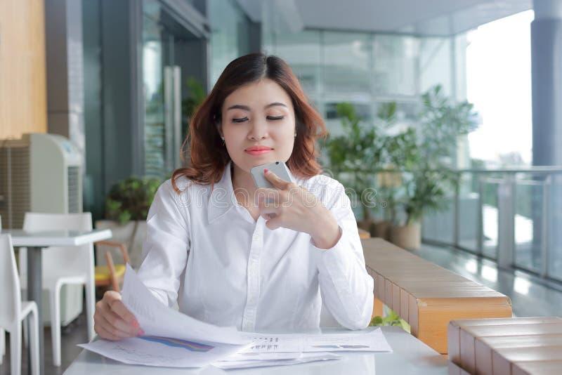 Portrait de la jeune femme asiatique d'affaires de beauté analysant des écritures ou des diagrammes sur le bureau dans le bureau photos stock