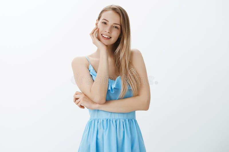 Portrait de la jeune femme belle sensuelle et sûre touchant la peau propre et brillante inclinant le chef souriant doucement à photographie stock libre de droits