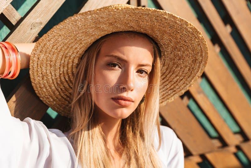 Portrait de la jeune femme blonde attirante 20s dans le chapeau de paille et un commutateur photo stock
