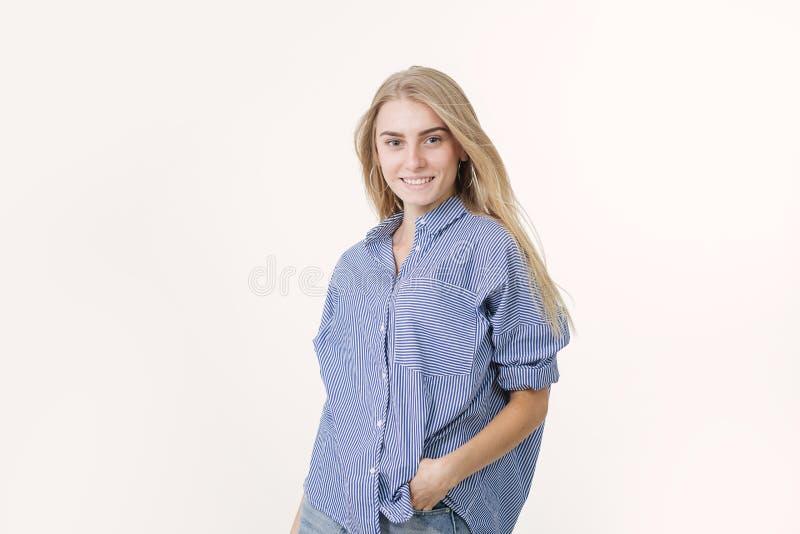 Portrait de la jeune femme blonde gaie utilisant la chemise bleue sur le fond blanc photo libre de droits