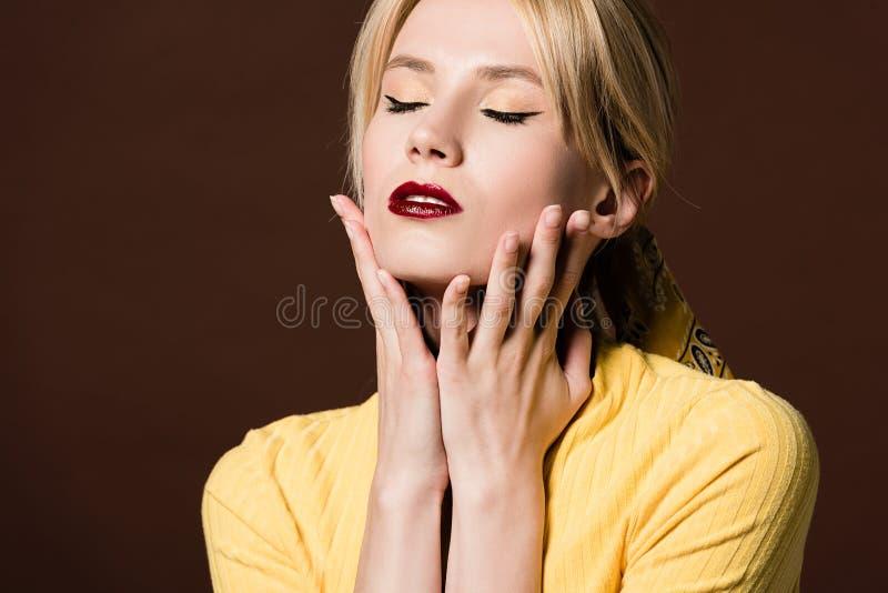 portrait de la jeune femme blonde séduisante touchant le visage avec des mains photographie stock