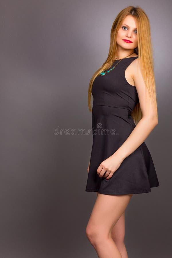 Portrait de la jeune femme blonde sexy portant une mini robe noire images libres de droits