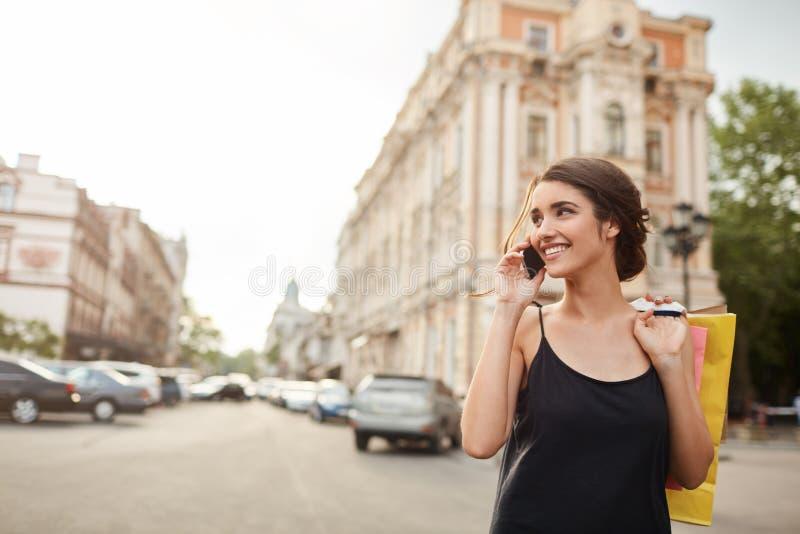 Portrait de la jeune femme caucasienne belle avec les cheveux foncés dans la robe noire se réveillant autour de la ville, parlant images libres de droits