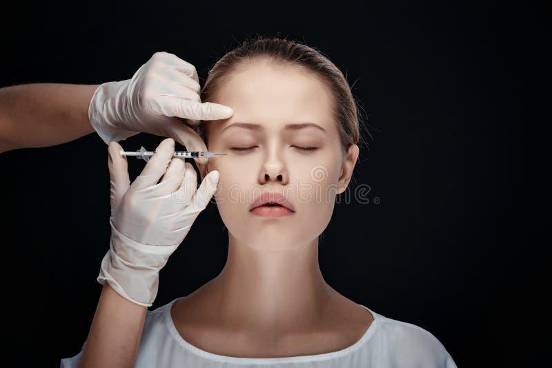 Portrait de la jeune femme caucasienne obtenant l'injection cosmétique images libres de droits