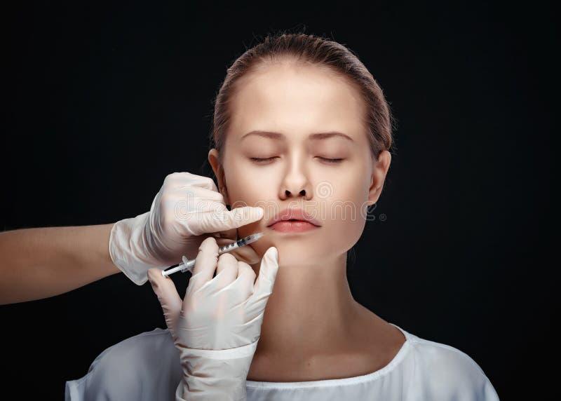 Portrait de la jeune femme caucasienne obtenant l'injection cosmétique photos stock