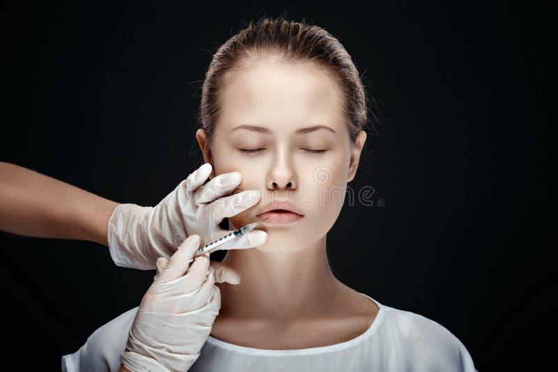 Portrait de la jeune femme caucasienne obtenant l'injection cosmétique photographie stock
