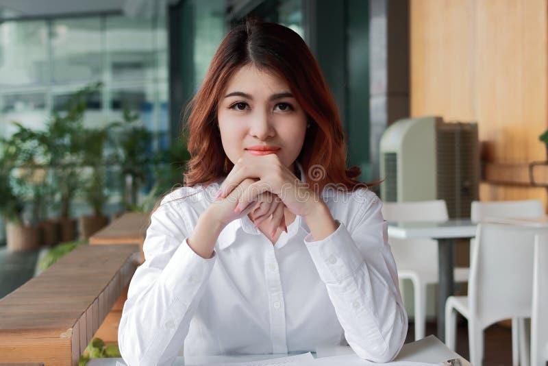 Portrait de la jeune femme d'affaires asiatique sûre regardant sur l'appareil-photo l'espace de travail à l'arrière-plan de burea photographie stock