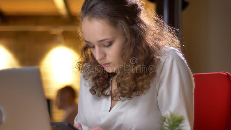 Portrait de la jeune femme d'affaires concentrée s'asseyant devant l'ordinateur portable et observant dans le smartphone sur le b images libres de droits