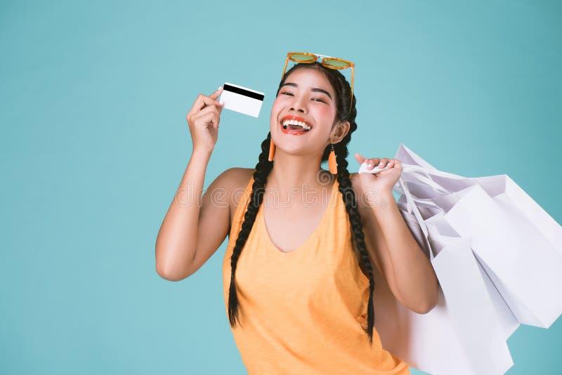Portrait de la jeune femme gaie de brune tenant la carte de crédit et les paniers images stock