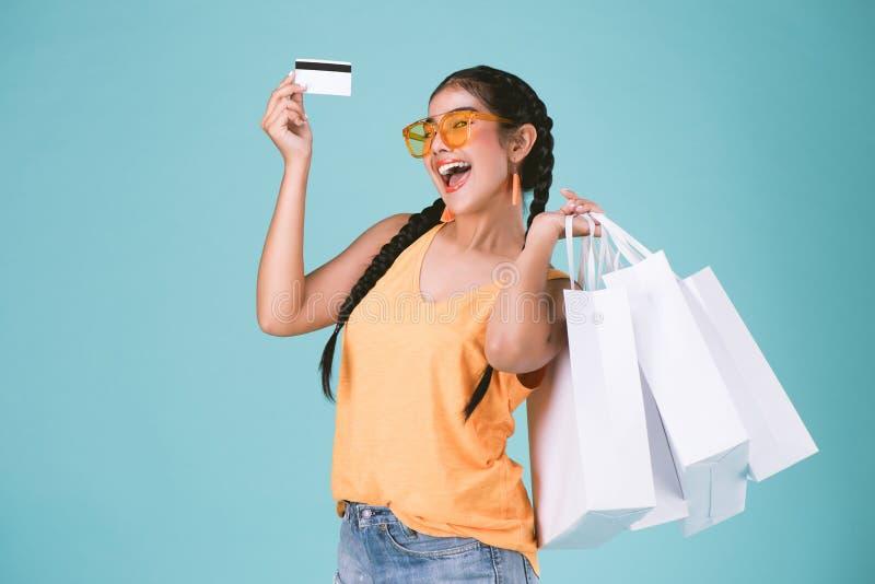 Portrait de la jeune femme gaie de brune tenant la carte de crédit et les paniers photo libre de droits