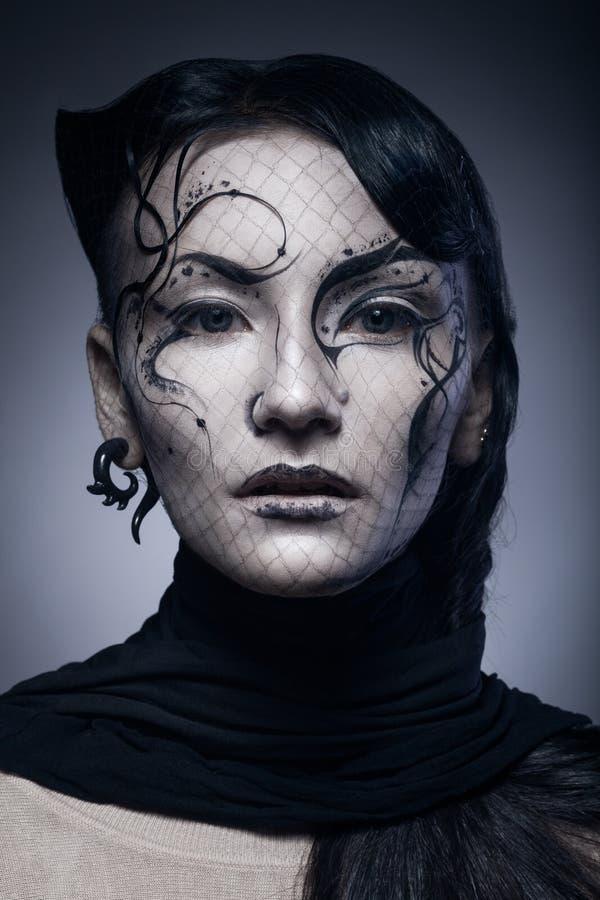 Portrait de la jeune femme gothique d'isolement sur l'obscurité photos stock