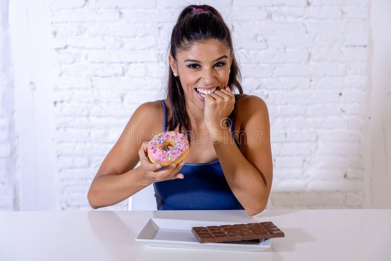 Portrait de la jeune femme heureuse mangeant la barre et les butées toriques de chocolat avec plaisir photographie stock libre de droits