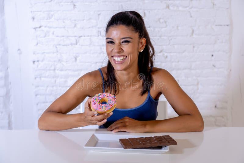 Portrait de la jeune femme heureuse mangeant la barre et les butées toriques de chocolat avec plaisir image stock