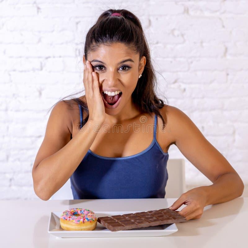 Portrait de la jeune femme heureuse mangeant la barre et les butées toriques de chocolat avec plaisir images stock