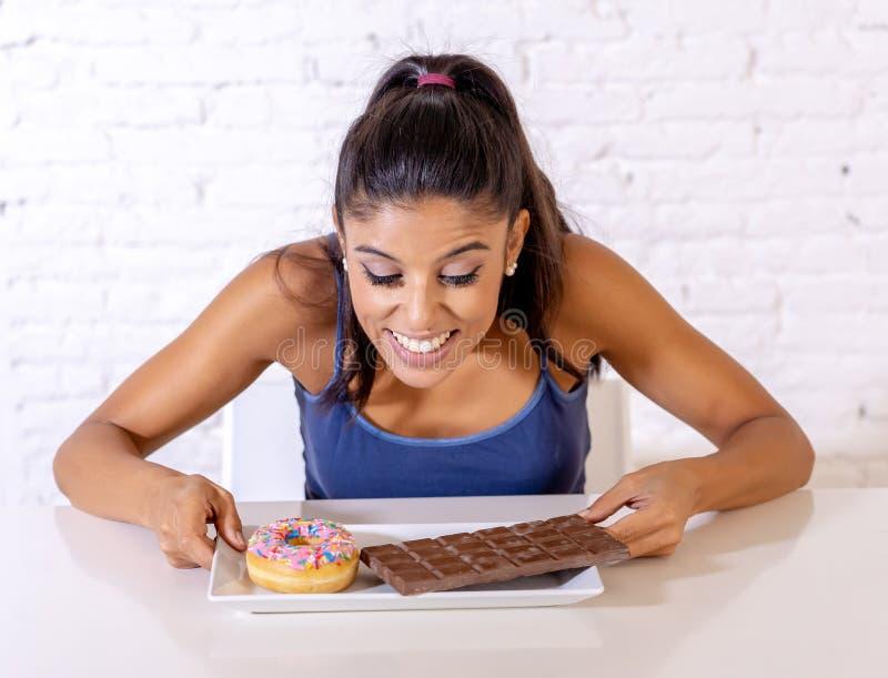 Portrait de la jeune femme heureuse mangeant la barre et les butées toriques de chocolat avec plaisir photo libre de droits