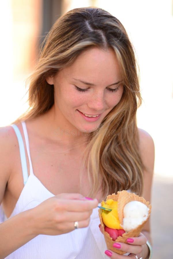 Portrait de la jeune femme heureuse mangeant de la glace extérieure photographie stock libre de droits