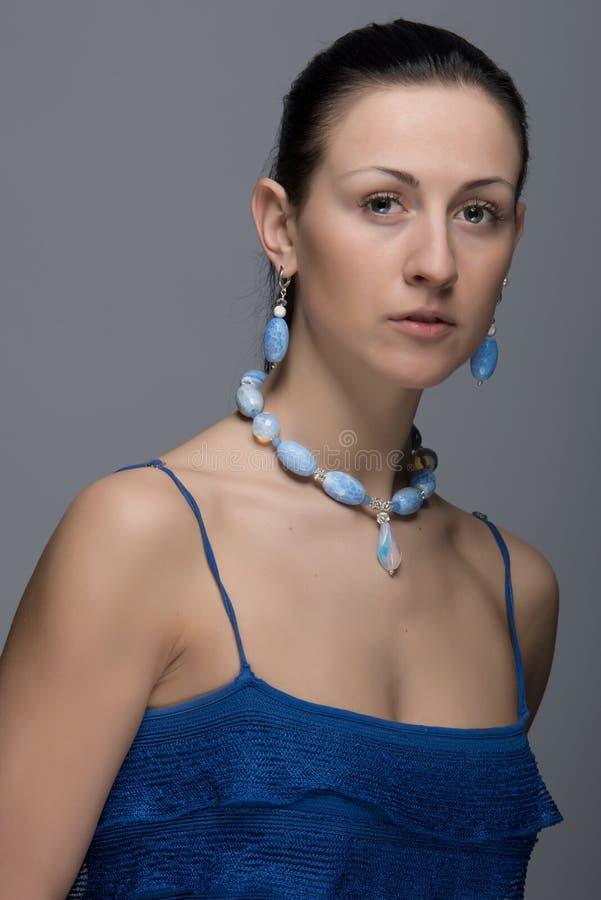 Portrait de jeune dame avec les boucles d'oreille et le collier images stock