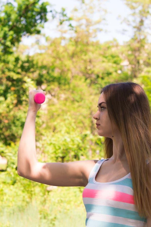 Portrait de la jeune femme mignonne dans l'usage de forme physique s'exerçant avec le dum photos stock