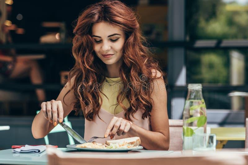 portrait de la jeune femme prenant le déjeuner seul image stock