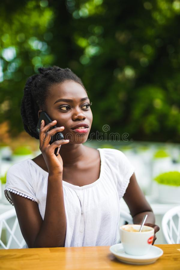 Portrait de la jeune femme de sourire d'afro-américain parlant au téléphone au café extérieur photos libres de droits