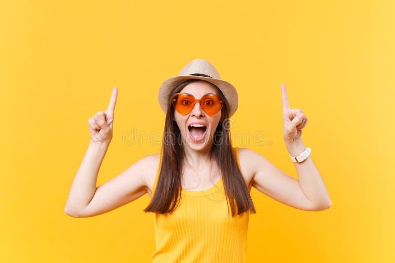 Portrait de la jeune femme de sourire dans le chapeau d'été de paille, verres oranges dirigeant des index sur l'espace de copie d photos libres de droits