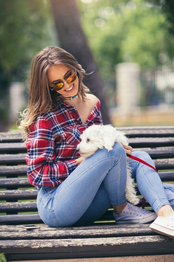Portrait de la jeune femme de sourire heureuse attirante tenant le petit chien mignon images stock