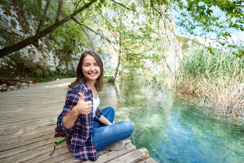 Portrait de la jeune femme de touristes de sourire s'asseyant sur le pont en bois, montrant des pouces  images stock