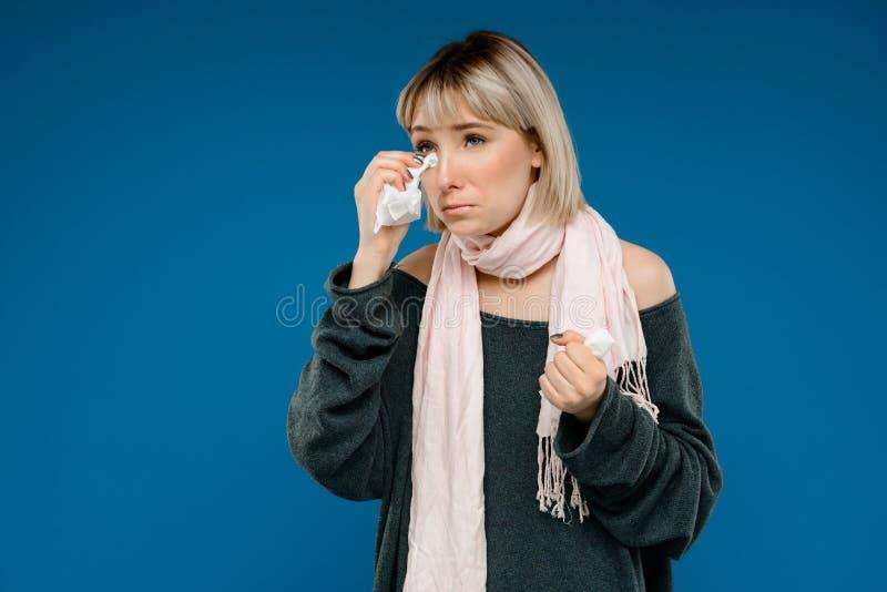 Portrait de la jeune fille étant malade au-dessus du fond bleu photographie stock libre de droits