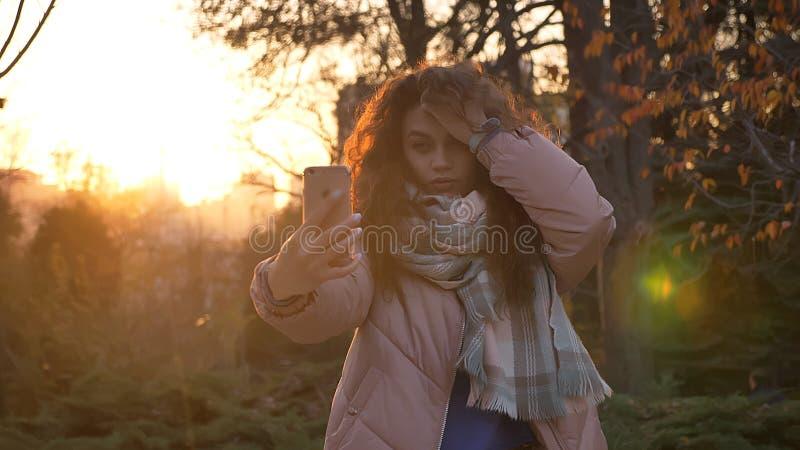Portrait de la jeune fille caucasienne ajustant ses cheveux et faisant des selfie-photos utilisant le smartphone en parc automnal images libres de droits