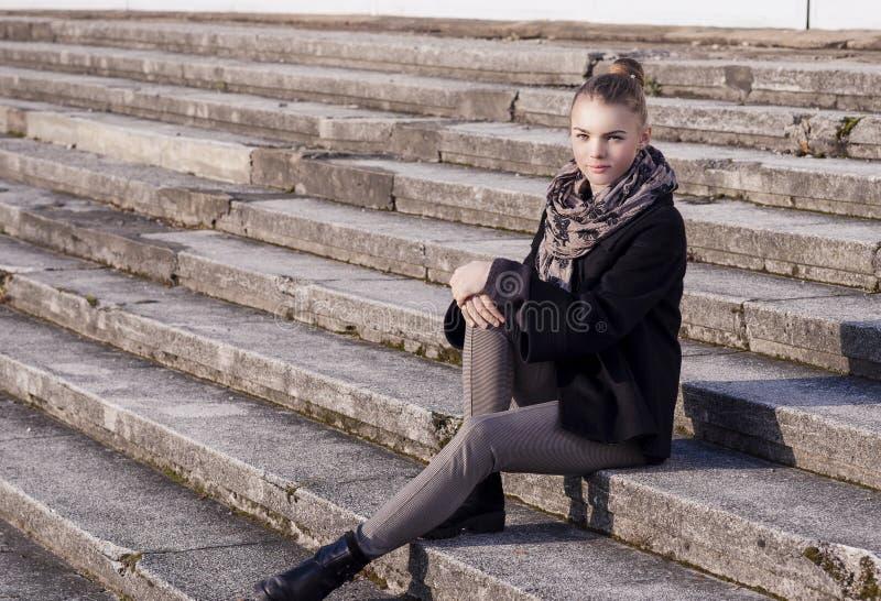 Portrait de la jeune fille caucasienne d'adolescent s'asseyant sur des escaliers Outd image libre de droits
